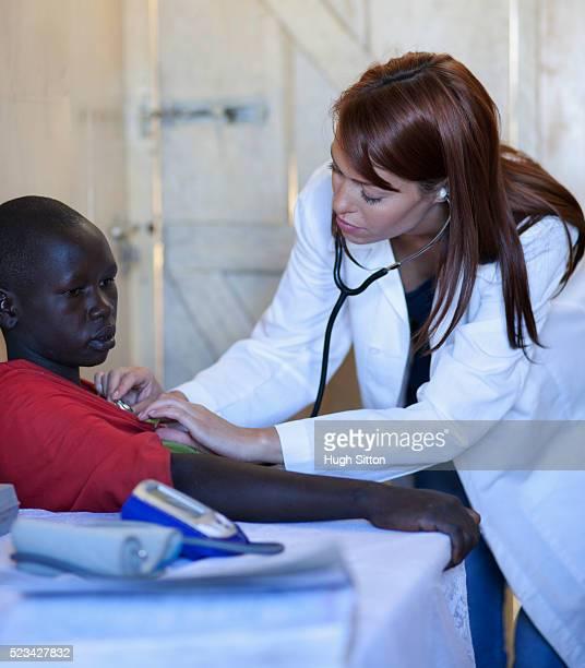 doctor using stethoscope with patient in clinic, kenya - hugh sitton - fotografias e filmes do acervo