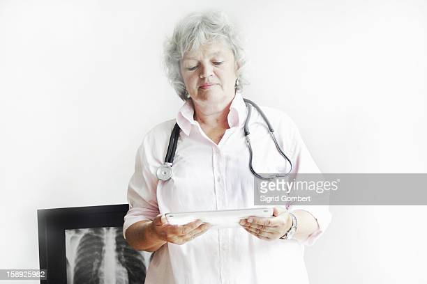 doctor using tablet computer in office - sigrid gombert stock pictures, royalty-free photos & images