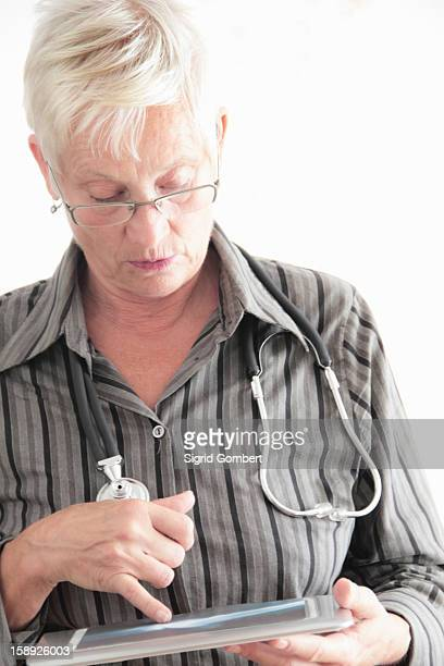 doctor using tablet computer in office - sigrid gombert stock-fotos und bilder
