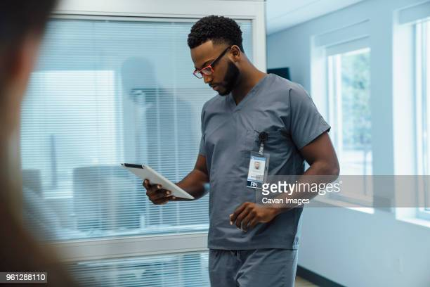 Doctor using tablet computer while walking in hospital