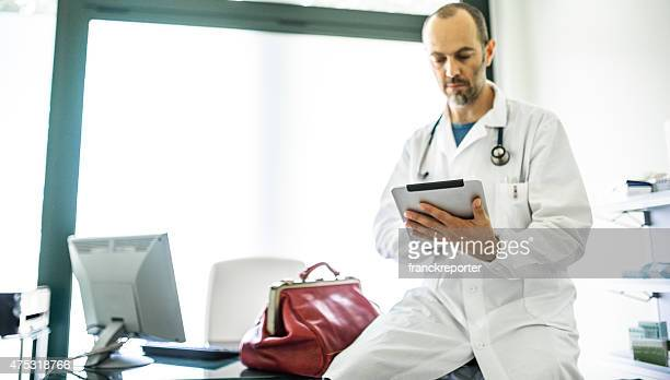 Doctor using the tablet on his office