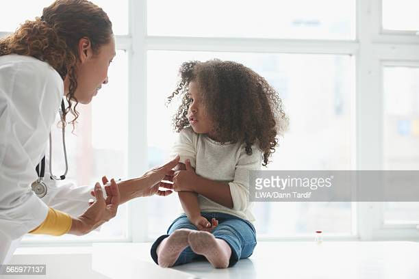 Doctor vaccinating girl in office