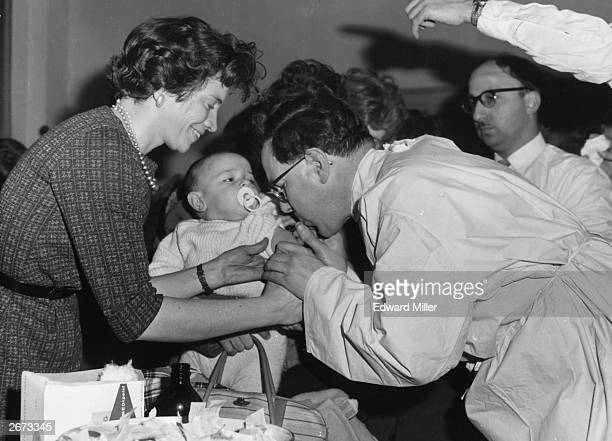 Doctor vaccinating one year old Tommy Riscoli at St Pancras Town Hall, London after a smallpox scare in Bradford, Yorkshire.