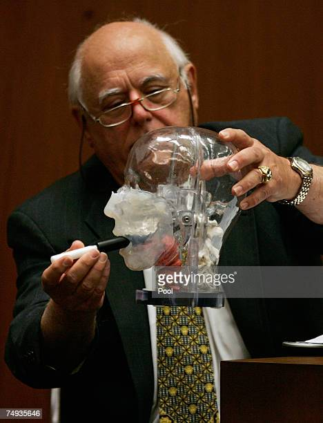 Doctor Vincent DiMaio a forensic expert on gunshot wounds puts a plastic rod into a dummy head during Phil Spector's murder trial at the Los Angeles...