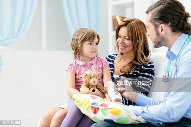 Arzt Besuch ein niedliches kleines Mädchen mit gebrochenen arm wie zu Hause fühlen.