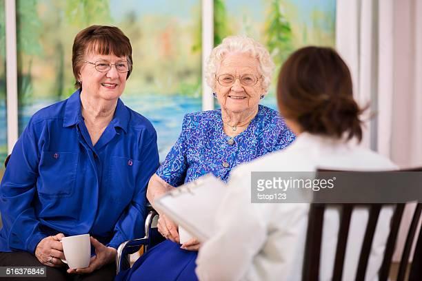 Doctor visits with elderly women patients in nursing home.