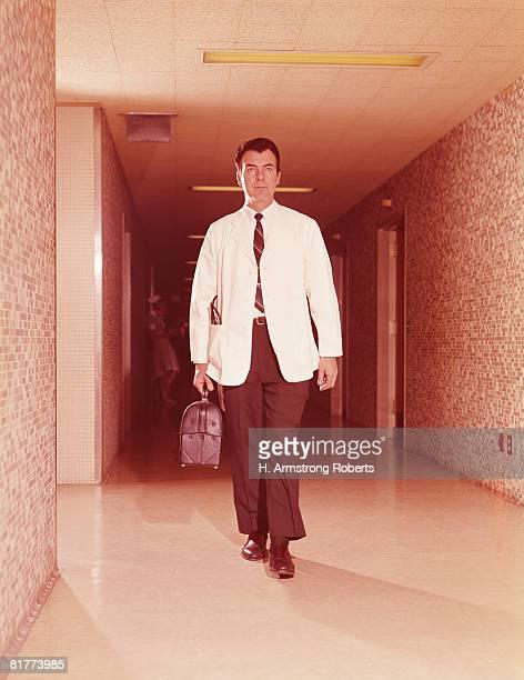 doctor walking along hospital corridor, carrying bag. (photo by h. armstrong roberts/retrofile/getty images) - dokterstas stockfoto's en -beelden