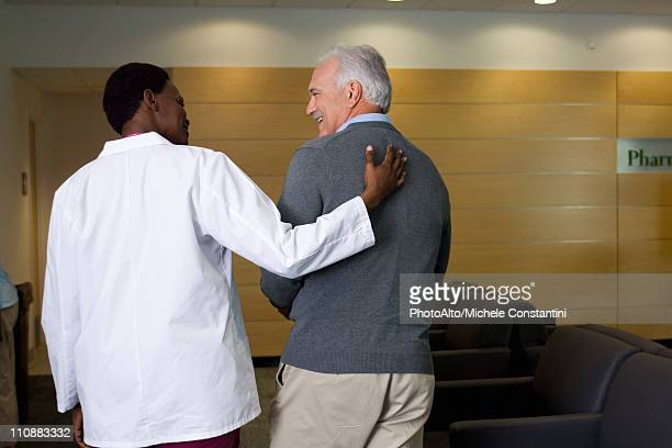 Doctor walking and talking with patient
