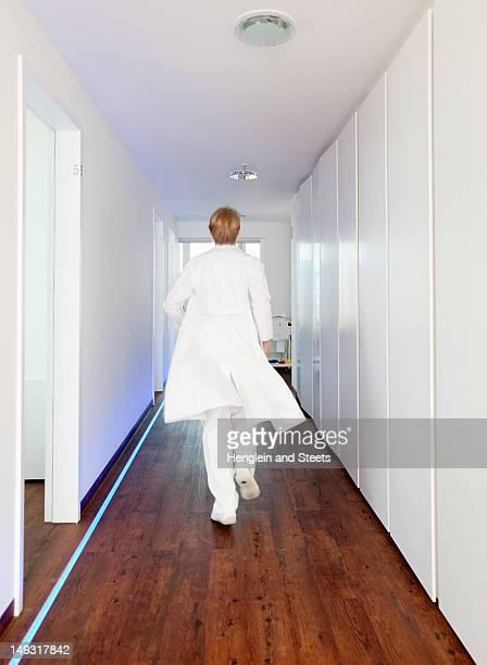 doctor walking in hallway - laborkittel stock-fotos und bilder