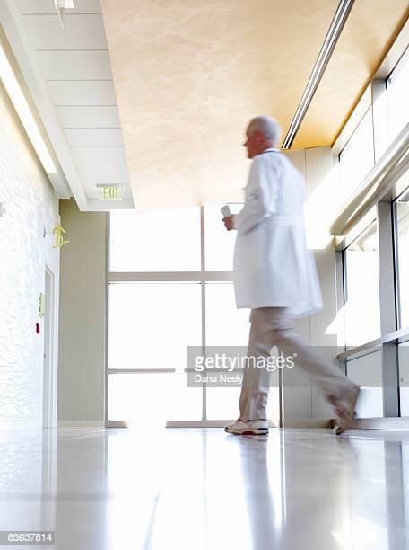 Doctor walking in hospital corridor, motion blur