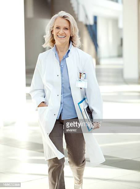 Doctor walking through the corrider of hospital with digital tablet