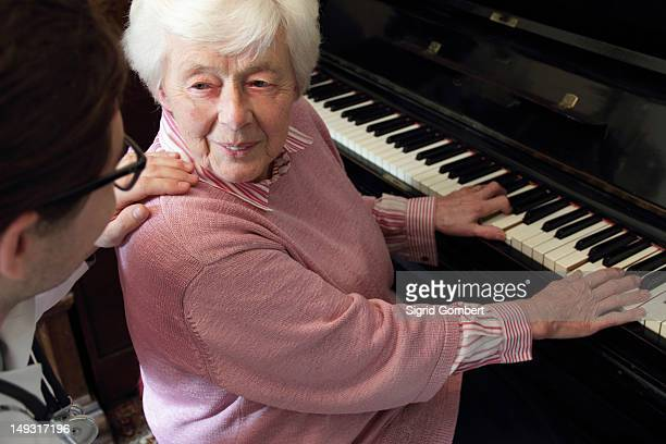 Doctor watching older woman play piano