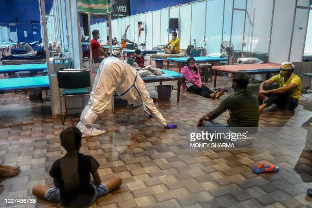 Doctor wearing a Personal Protective Equipment suit instructs patients as they perform yoga inside a ward at the Commonwealth Games Village sports...
