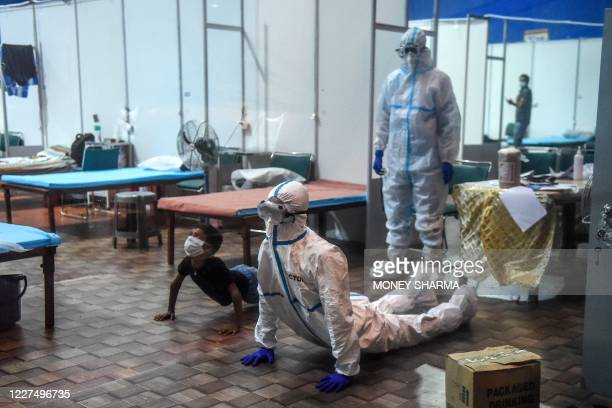 TOPSHOT A doctor wearing a Personal Protective Equipment suit performs yoga with a young patient inside a ward at the Commonwealth Games Village...