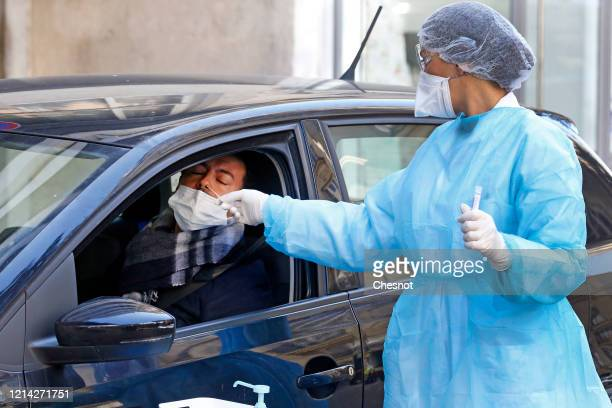 A doctor wearing a protective mask protective glasses and protective gloves takes sample from patients using a drivethrough coronavirus testing...