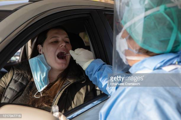 A doctor wearing a protective suit offers a mouth and nose swab through a car window at a 'drivethrough' coronavirus testing facility at Ospedale...