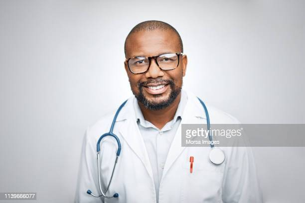 doctor wearing eyeglasses on white background - dokter stockfoto's en -beelden