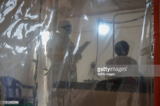 A doctor wearing full protective gear speaks to a patient in the Ebola treatment centre in Beni eastern Democratic Republic of the Congo The DRC is...
