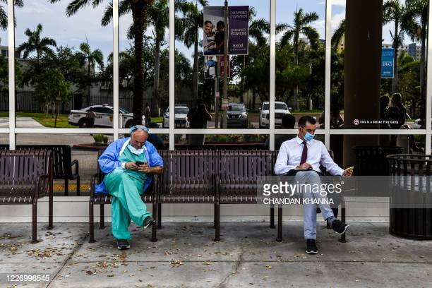 Doctor wearing personal protective equipment uses his mobile phone as he sits outside Jackson Memorial Hospital in Miami, on July 13, 2020. - Virus...