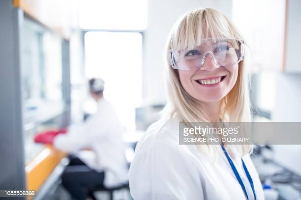 doctor wearing protective goggles and smiling - wissenschaft stock-fotos und bilder