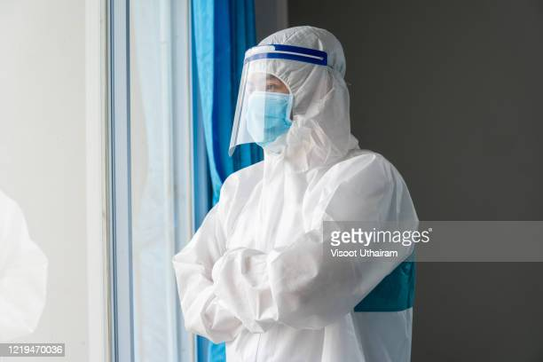 doctor wearing protective suit to fight coronavirus pandemic covid-2019. - protective suit stock pictures, royalty-free photos & images