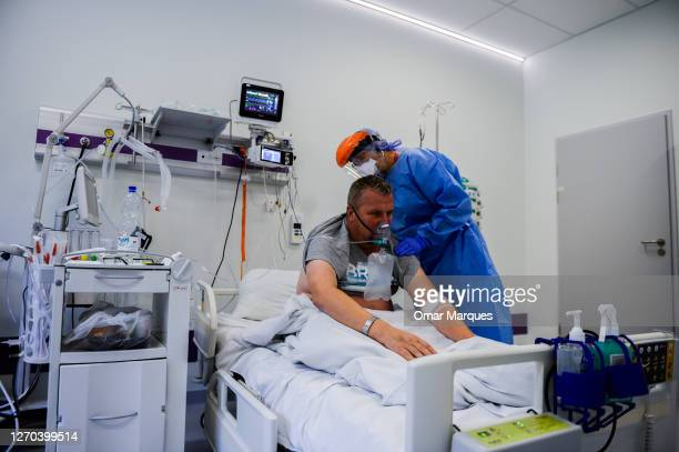 Doctor wears a protective suit, mask, gloves and a face shield as she checks the lungs of a COVID-19 patient at the Krakow University Hospital on...