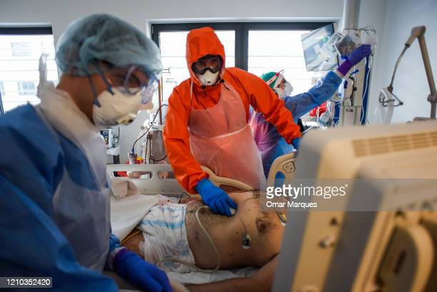 Doctor wears a protective suit, mask, goggles and gloves as he performs an ultrasound scan on a COVID - 19 patient inside the Intensive Care Unit for...