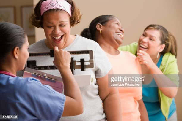 Doctor weighing a delighted woman