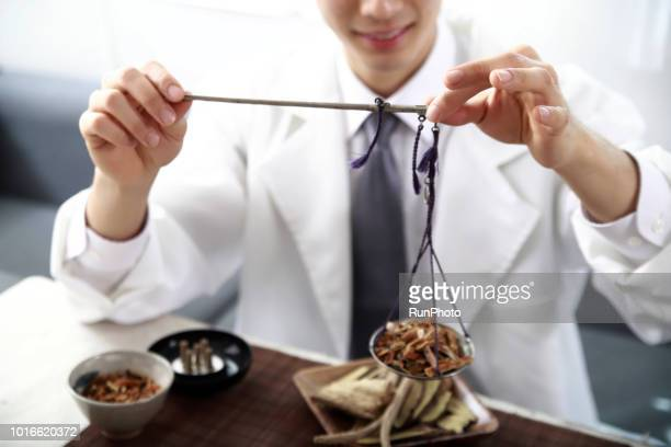 Doctor weighing herbal medicines with scales