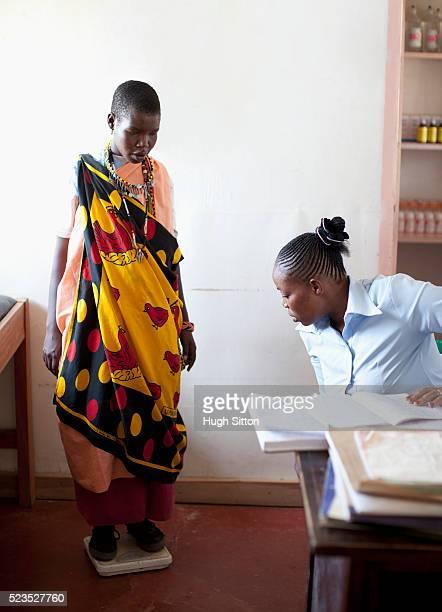 doctor weighing patient in clinic - hugh sitton stock-fotos und bilder