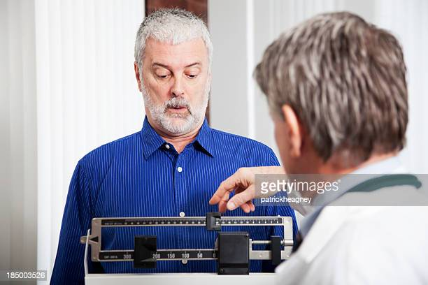 doctor weighing patient - mass unit of measurement stock pictures, royalty-free photos & images
