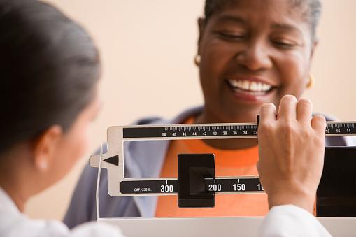 Doctor weighing woman - gettyimageskorea