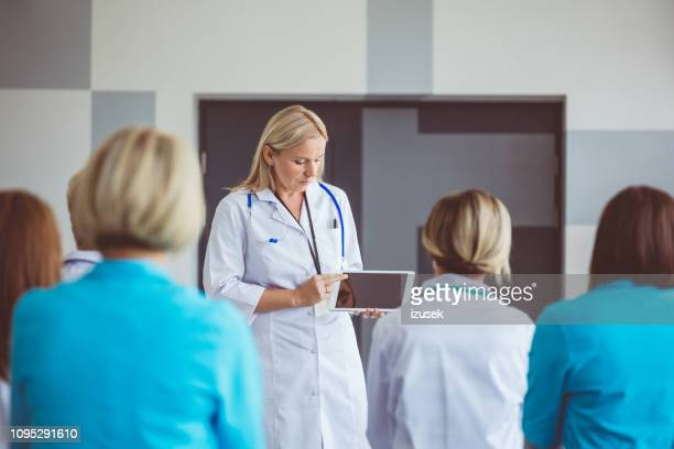 doctor with a digital tablet addressing a medical team - izusek stock pictures, royalty-free photos & images