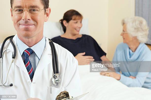 Doctor with a pregnant woman and a family member