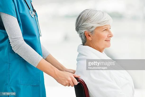Médecin avec le patient senior en fauteuil roulant