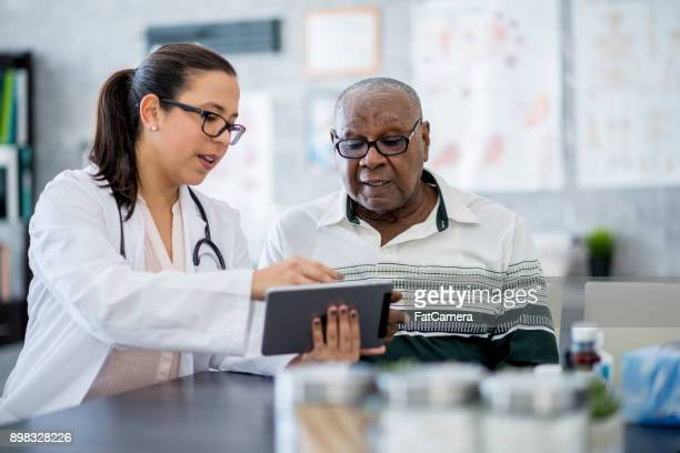 doctor with a tablet computer - senior adult stock pictures, royalty-free photos & images