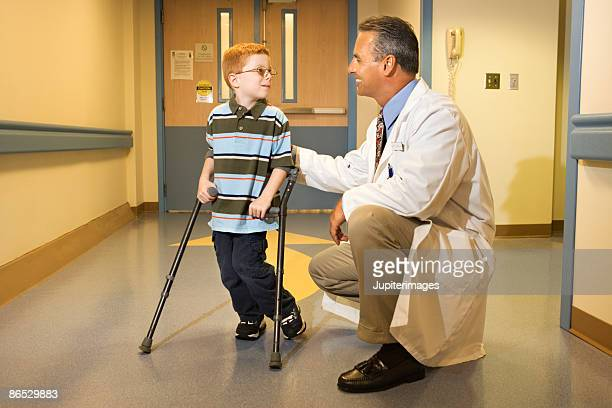 doctor with boy on crutches - crutches stock photos and pictures