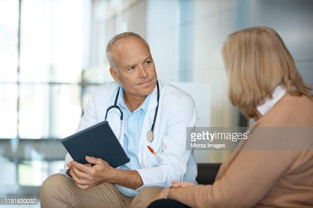 doctor with digital tablet looking at woman - visit stock pictures, royalty-free photos & images
