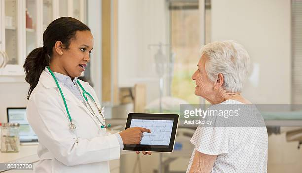 doctor with digital tablet talking to patient - medical chart stock pictures, royalty-free photos & images