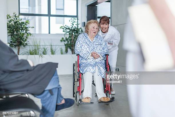 Doctor with elderly patient in wheelchair on hospital floor