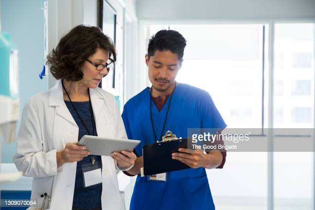 doctor with male nurse holding digital tablet while discussing in hospital corridor - healthcare stock pictures, royalty-free photos & images
