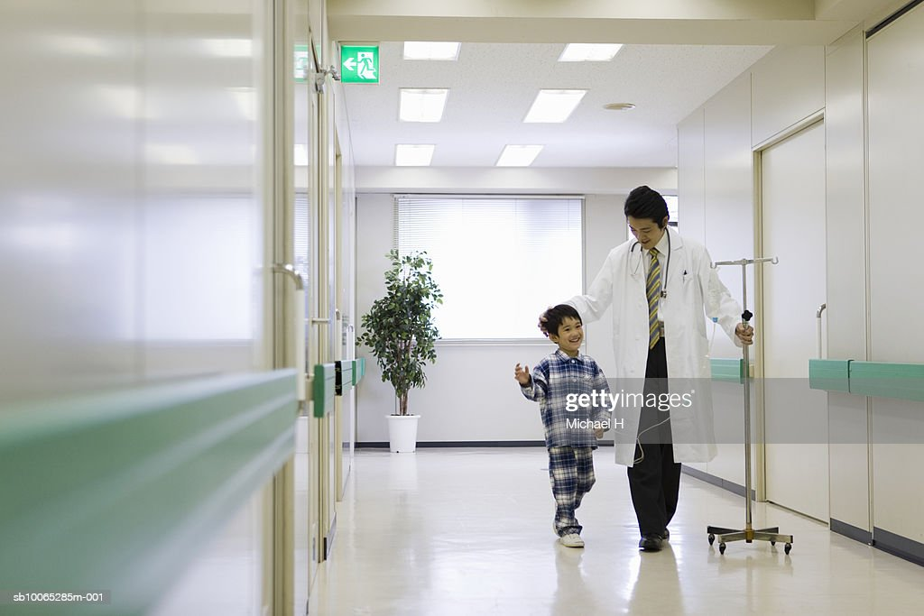 Doctor with medicine drip, walking with boy (5-6) in hospital corridor : Foto stock