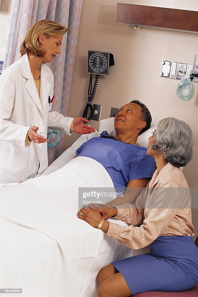 Doctor with patient and his wife : Stockfoto