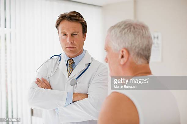 doctor with patient in doctors office - arrogance stock pictures, royalty-free photos & images