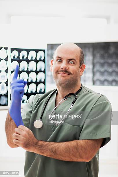 doctor with purple glove and wide-eyed look - purple glove stock pictures, royalty-free photos & images