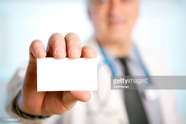 Doctor with stethoscope around his neck showing a blank card