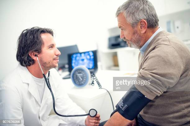 Doctor with stethoscope measuring a patient's blood pressure