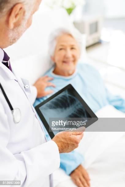 Arzt mit X-Ray auf digitale Tablet Trösten Patienten im Krankenhaus