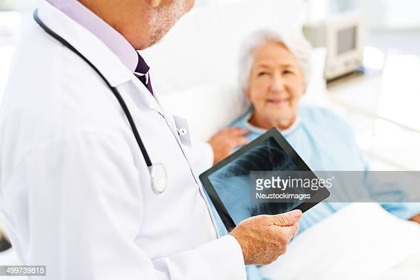Doctor With X-Ray On Tablet Computer Consoling Patient In Hospit