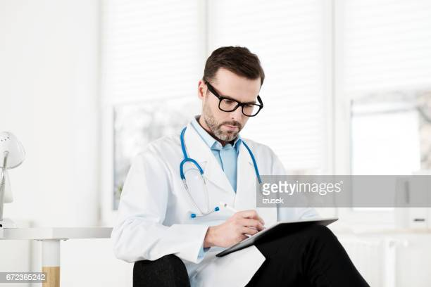 doctor working in his office - izusek stock pictures, royalty-free photos & images